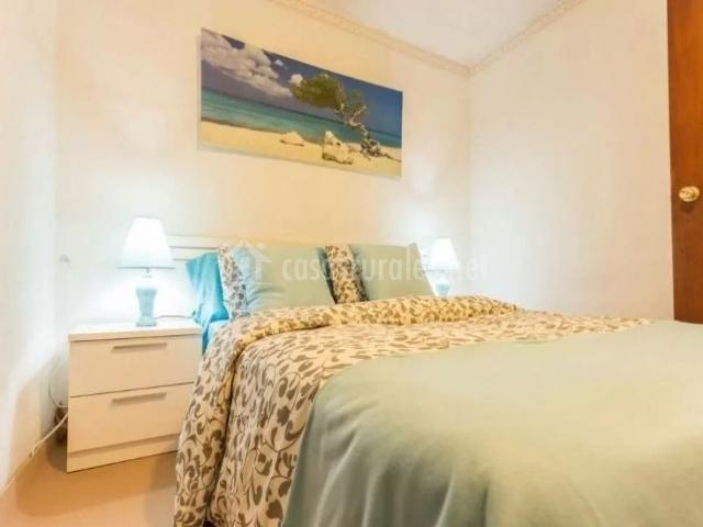 Dormitorio de matrimonio con cuadro sobre la cama