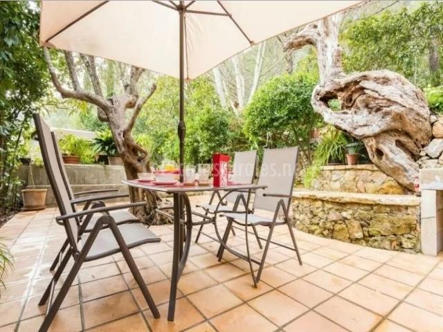 Vistas de la terraza con sombrilla y mesa con sillas
