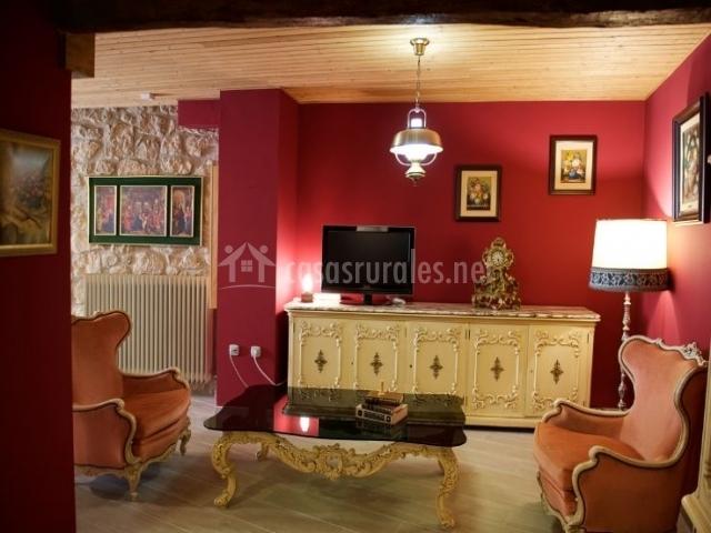 Sala de estar con televisor y mesa de cristal
