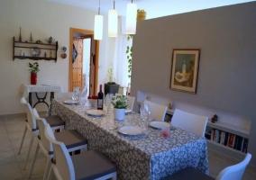 Comedor en tonos claros con mesa amplia y platos