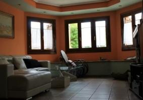 Sala de estar con sillones y mesa de cristal