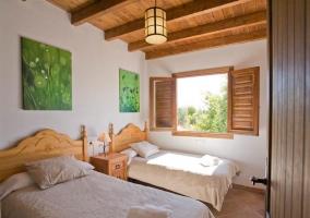 Dormitorio doble con cuadros verdes sobre los cabeceros