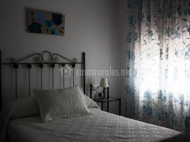 Dormitorio de matrimonio con colcha en blanco y cortina