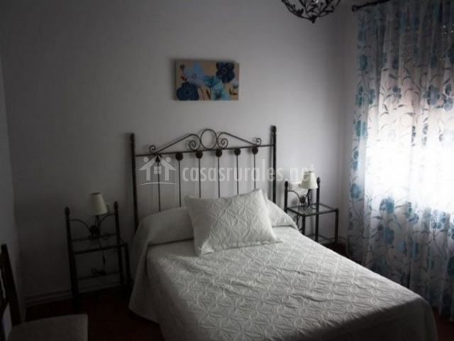 Dormitorio de matrimonio con colcha en blanco y cuadro