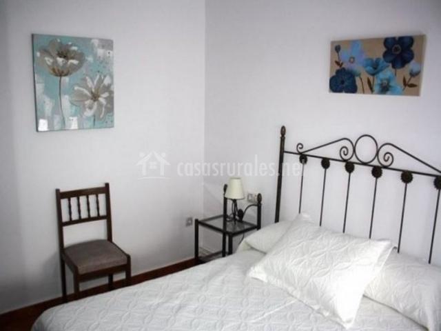 Dormitorio de matrimonio con colcha en blanco y cuadros