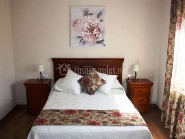 Dormitorio de matrimonio con mesillas y cojines de flores