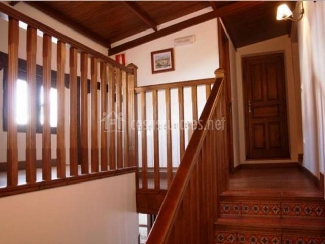 Pasillo con barandilla de madera y techos