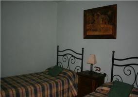 Dormitorio con dos camas individuales y pared azul
