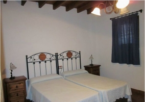 Dormitorio con dos camas individuales y vigas de madera
