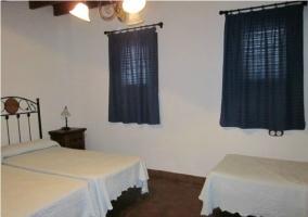 Dormitorio con tres camas y cortinas azules