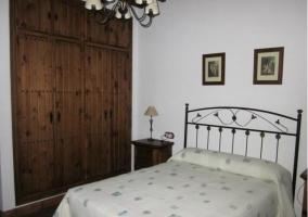 Dormitorio de matrimonio con cabecero de hierro y armario empotrado