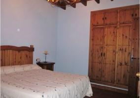 Dormitorio de matrimonio con cabecero y armario empotrado de madera