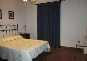 Dormitorio de matrimonio con edredón blanco y cortina azul