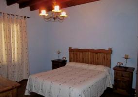Dormitorio de matrimonio con mobiliario de madera. Pared azul
