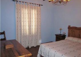 Dormitorio de matrimonio con pared azul y cortinas blancas