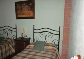 Dormitorio doble con edredones de cuadros y cabecero de hierro