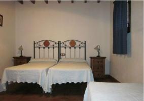 Dormitorio triple con edredones blancos y cortinas azules