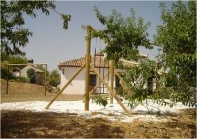 Zona de columpios de madera con arena