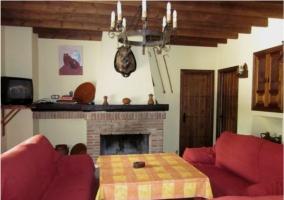 Zona de estar con sillones rojos y chimenea