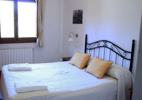 Dormitorio de matrimonio con toallas blancas y cojines