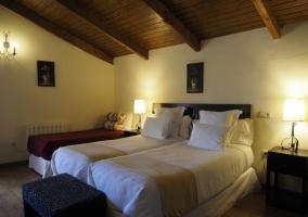 Dormitorio doble con techos abuhardillados y mesillas