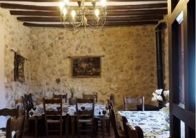 Sala de estar con mesa y paredes de piedra