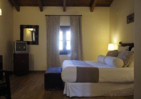 Dormitorio doble en blancos y marrones con televisor