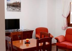 Sala de estar y comedor con sillones tapizados y estufa