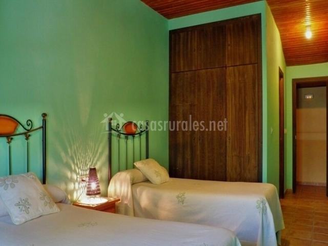 Habitación con 2 camas y pared verde
