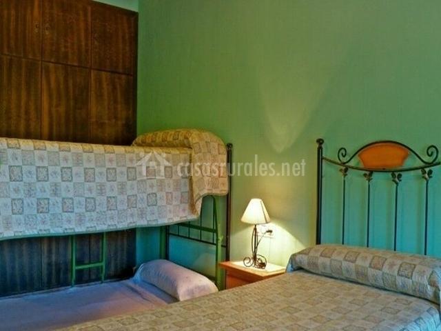Habitación triple con literas y pared verde