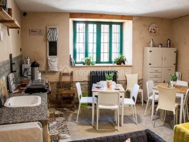 Cocina comedor con mesas y sillas blancas