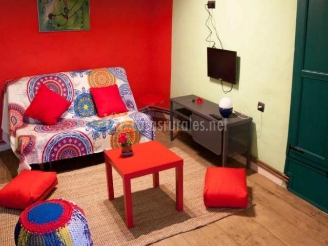 Dormitorio colorido con sala de estar y televisor