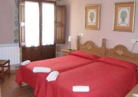 Dormitorio con paredes moradas y dos camas