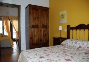 Dormitorio de matrimonio con colcha de flores y armario de madera