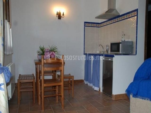 Cocina y comedor en azul con mesa de madera