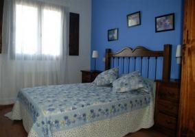 Dormitorio de matrimonio en color azul con cabecero de madera