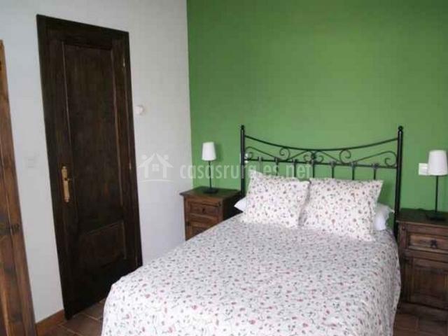 Dormitorio de matrimonio con pared de color verde