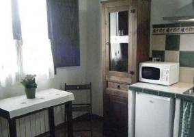 Cocina junto a la sala de estar en tonos verdes
