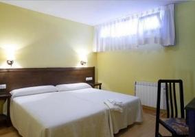 Dormitorio doble con un par de camas y mesillas