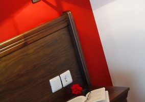 Dormitorio con cama de matrimonio y pared de color rojo