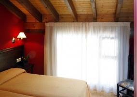 Dormitorio doble con camas individuales y pared de color rojo