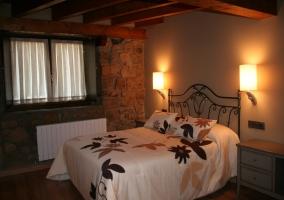 Dormitorios de piedra con amplio ventanal y cálida luz