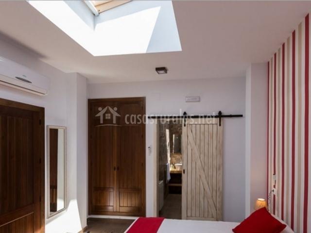 Dormitorio doble con detalles en rojo y tragaluz