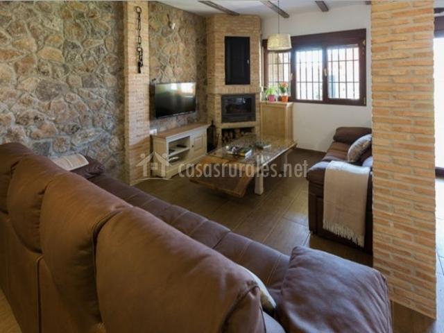 Sala de estar en la planta baja con chimenea y televisor