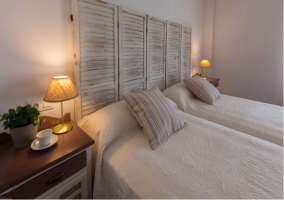 Dormitorio doble con detalles y mantas en morado