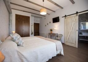 Dormitorio doble con gran marco y puerta de granero hacia el aseo