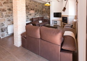 Sala de estar en la planta superior con pared de piedra