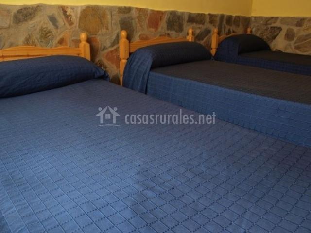 Dormitorio triple con colchas de color azul