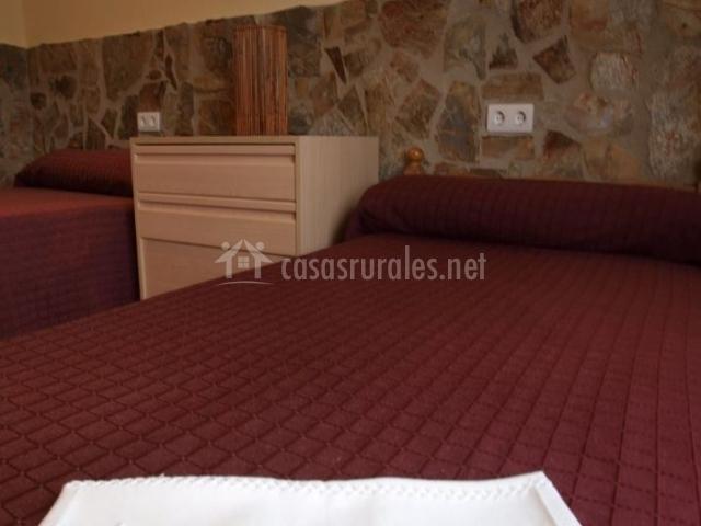Dormitorio triple con colchas en color burdeos