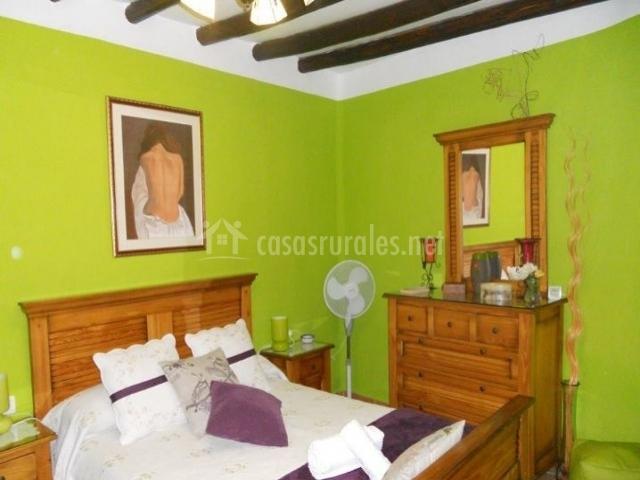 Dormitorio de matrimonio con paredes verdes y muebles de madera